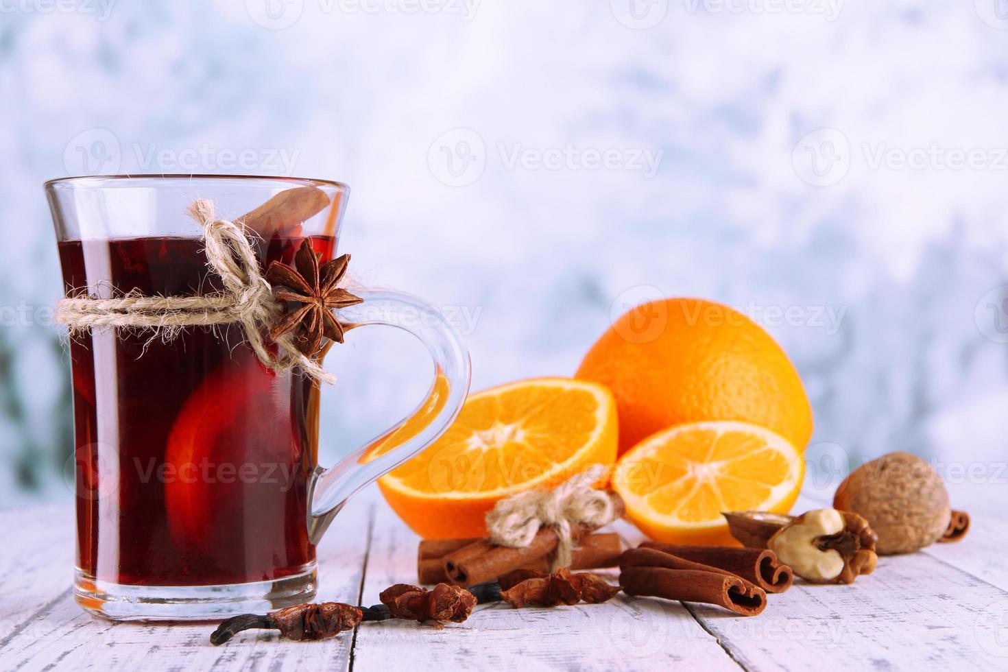 vinho quente com laranjas e especiarias na mesa foto