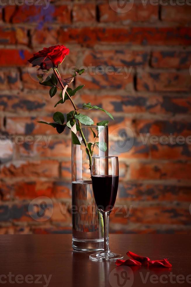 vaso com rosa e taça de vinho foto