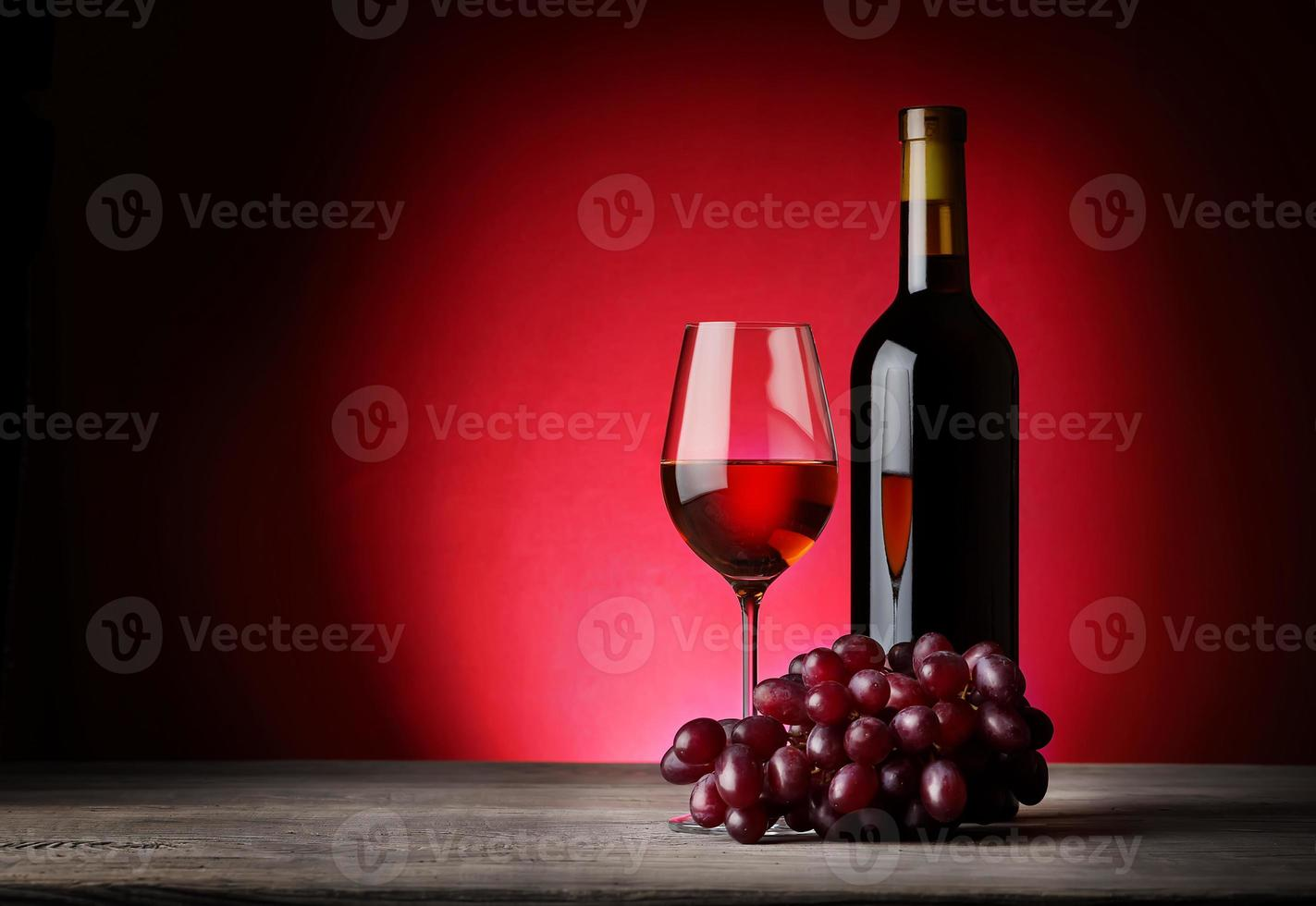 garrafa e taça de vinho com uvas foto