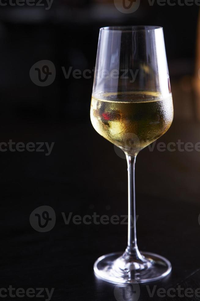 taça de vinho branco na mesa foto