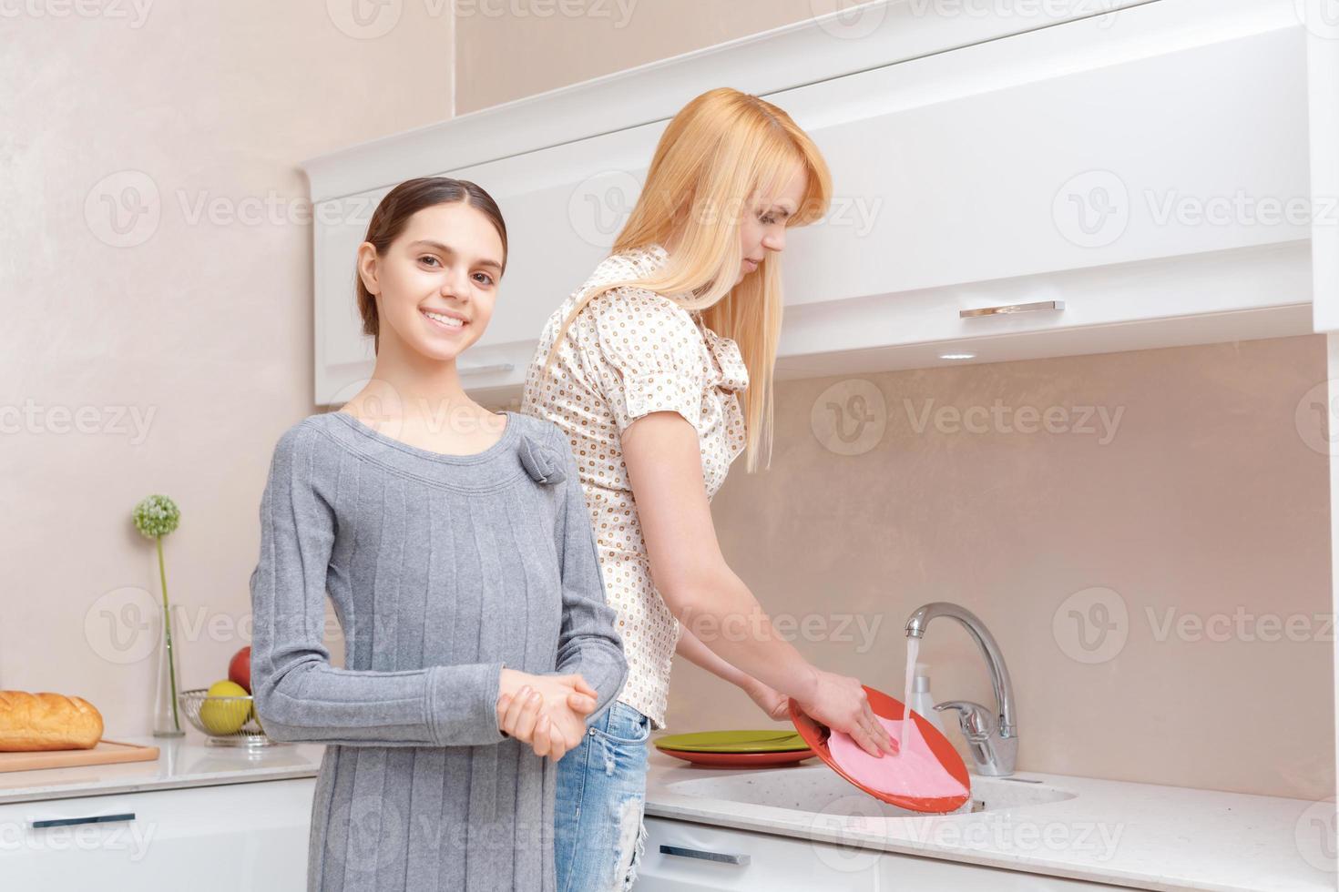 mãe e filha lavam pratos foto