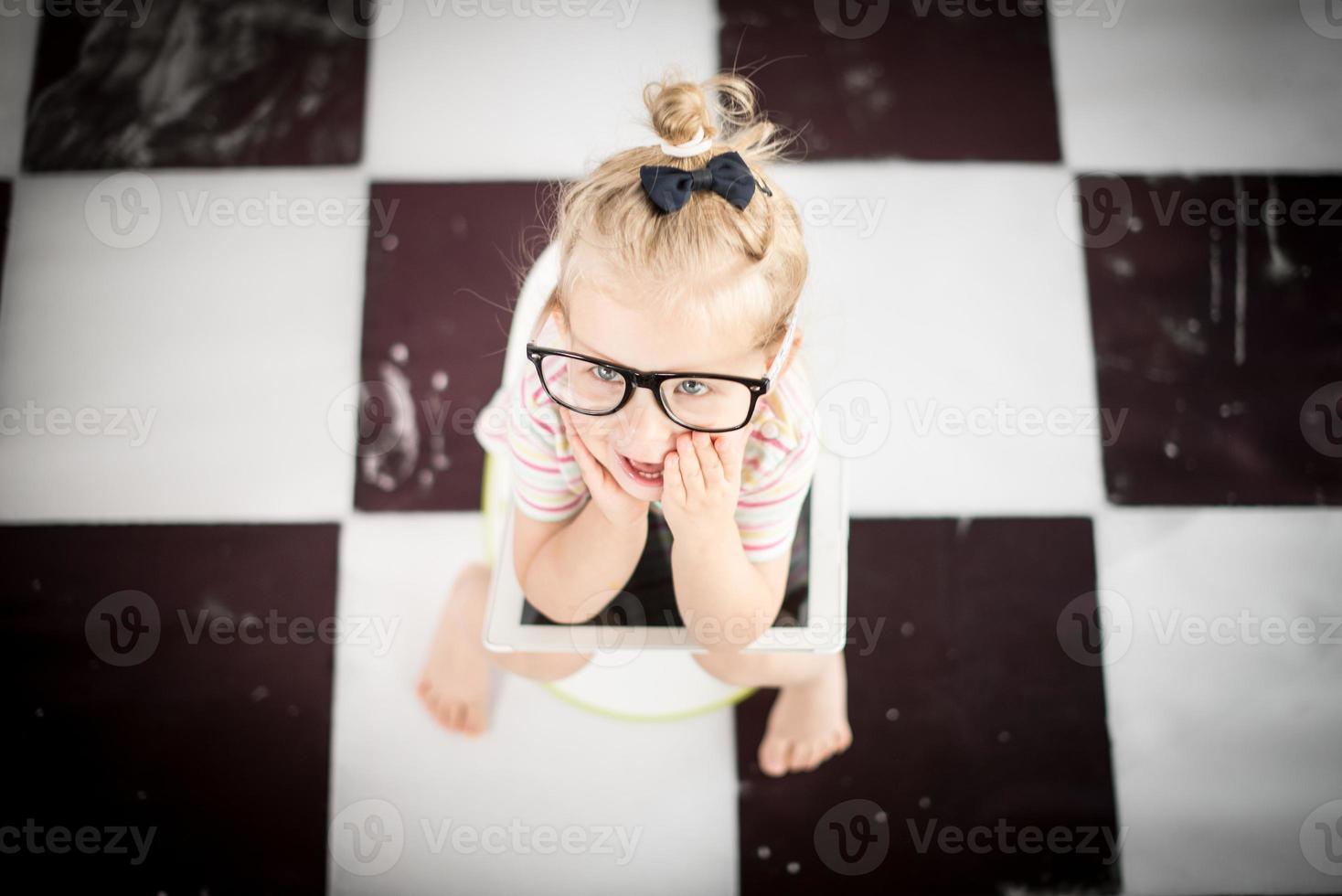 menina em um penico com tablet pc foto