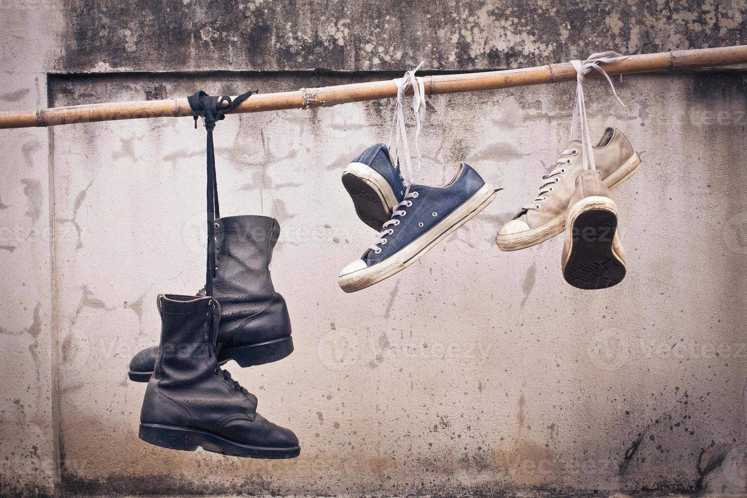 par de tênis velhos e bota velha pendurar foto