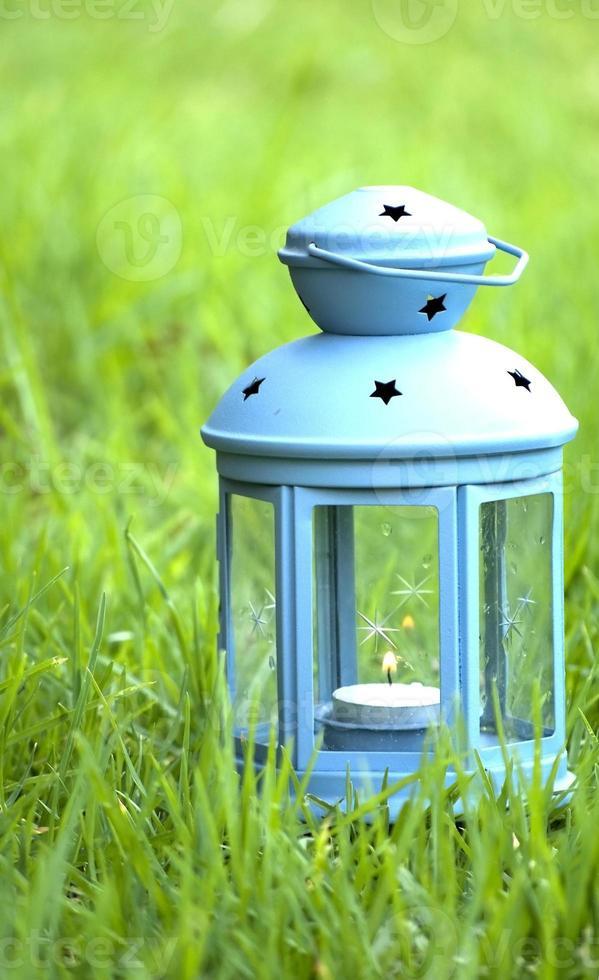 lanterna azul, com uma vela acesa dentro, na grama verde foto