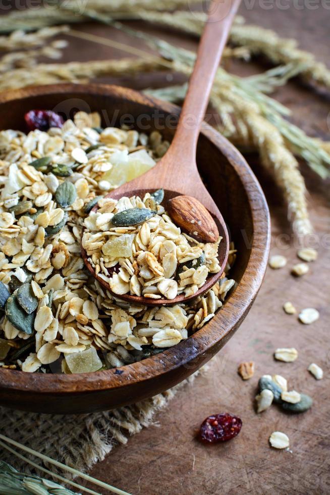 grãos de aveia e trigo integral em flocos em uma tigela de madeira foto