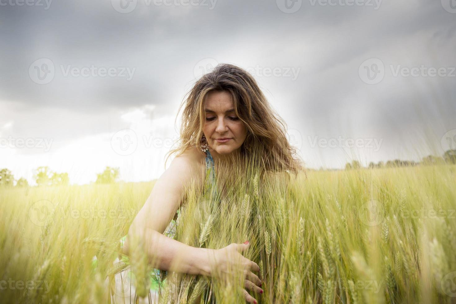 bela senhora abraçando espigas de trigo ao ar livre foto