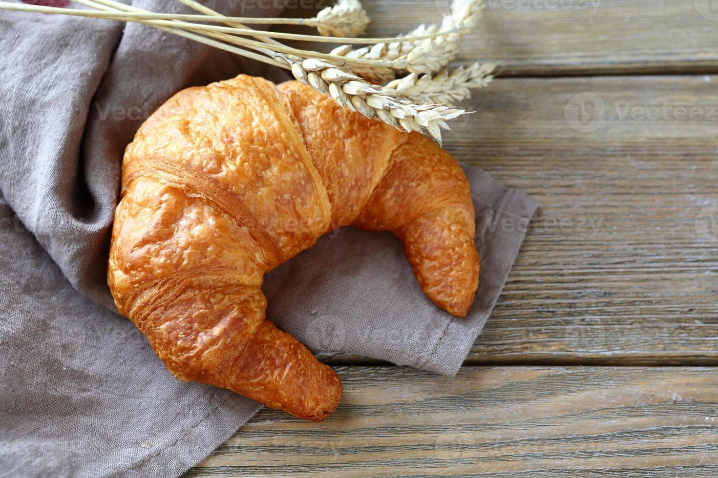 um croissant francês avermelhado nas tábuas foto