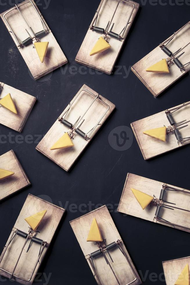 várias ratoeiras com queijo em um fundo escuro foto