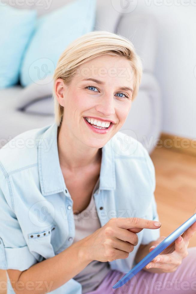 mulher loira bonita usando seu tablet no chão foto
