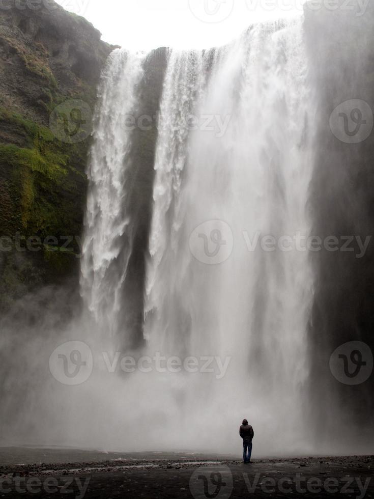 homem em frente a grande cachoeira foto