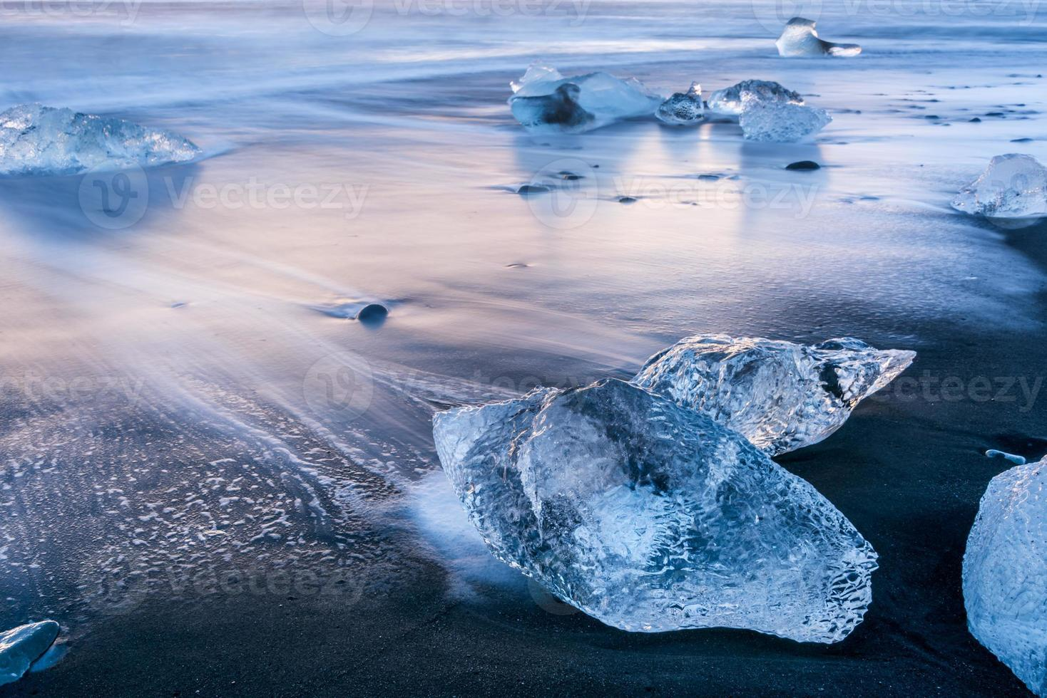 lindo gelo azul na praia de areia preta, jokulsarlon, Islândia foto