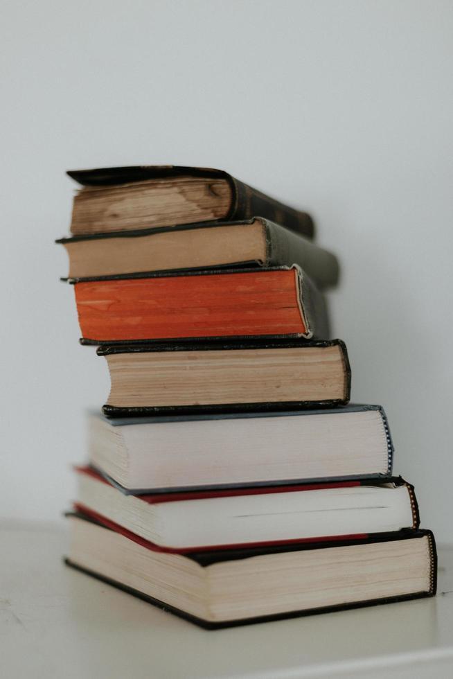 livros antigos empilhados na superfície branca foto