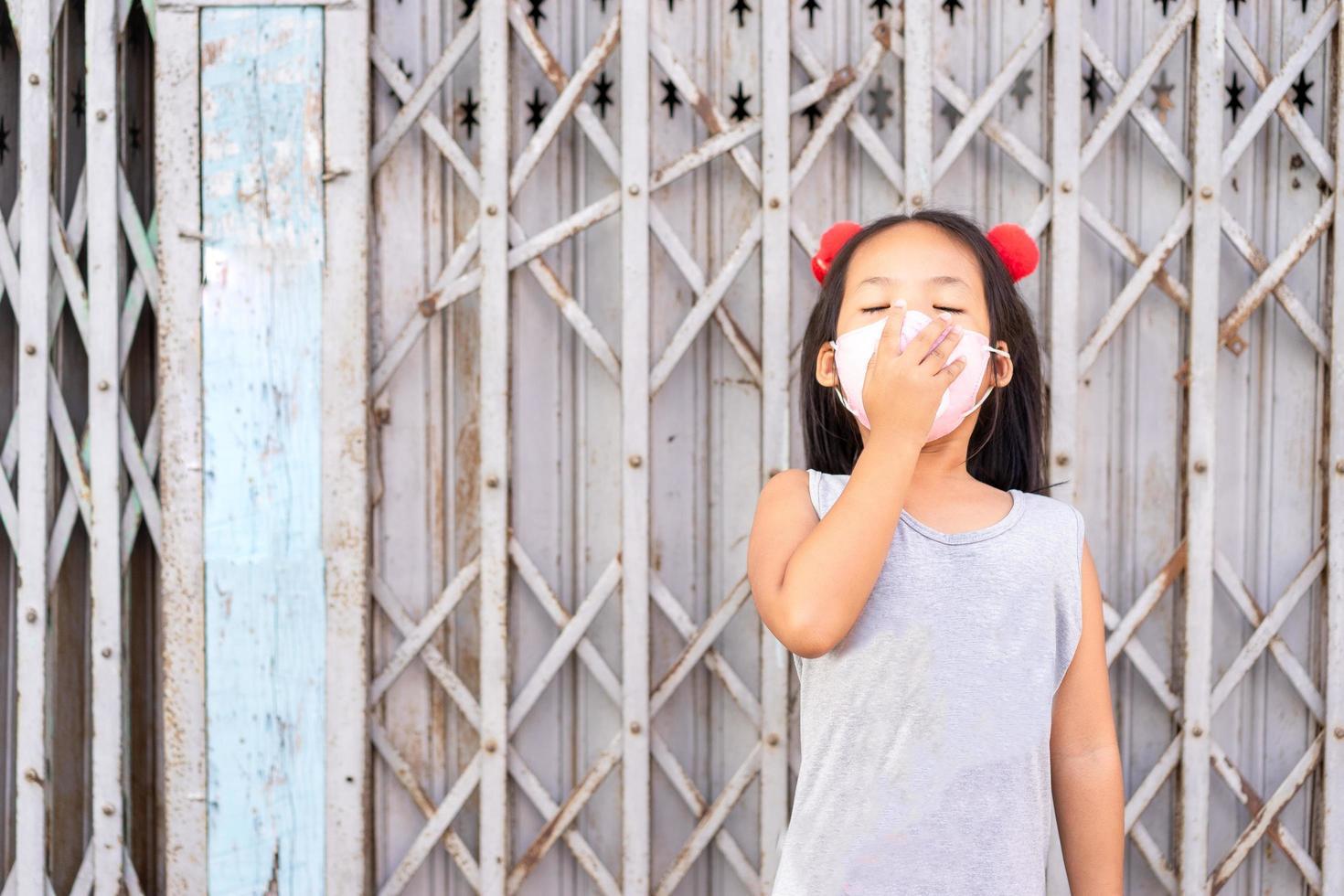 garotinha asiática bocejando com máscara foto