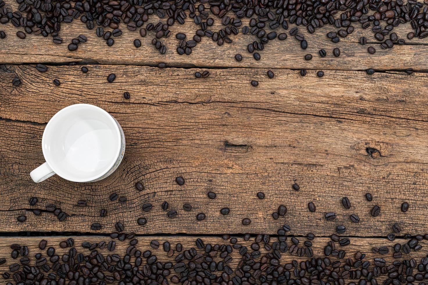 caneca vazia e grãos de café na mesa foto