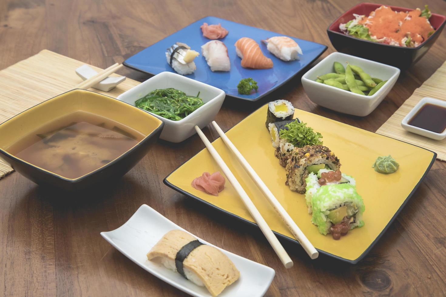 pratos de comida japonesa na mesa de madeira foto