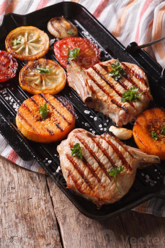 carne de porco grelhada, abóbora e limão em uma assadeira. vertical foto