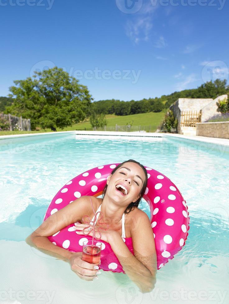 mulher rindo na piscina com bebida foto