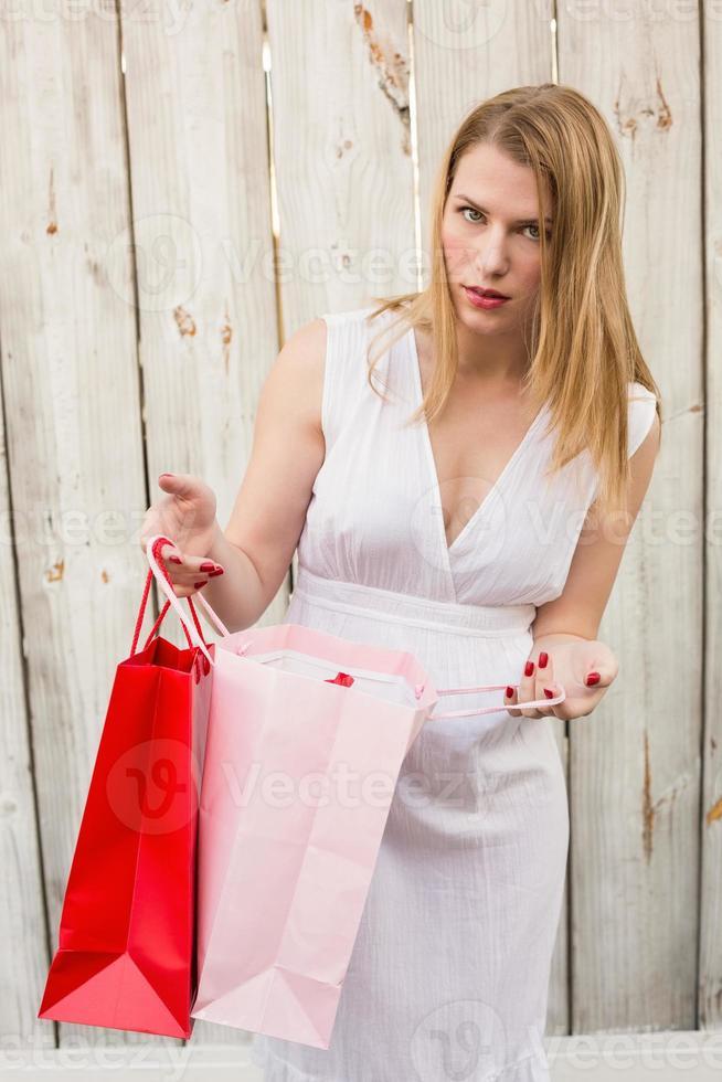 mulher loira abrindo uma sacola de presente enquanto olha para a câmera foto