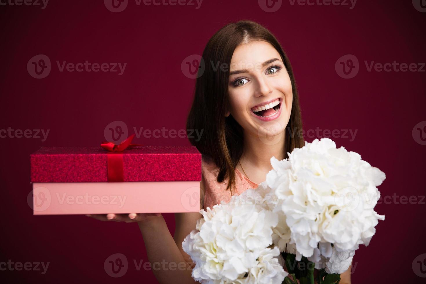 mulher bonita sorridente segurando uma caixa de presente e flores foto