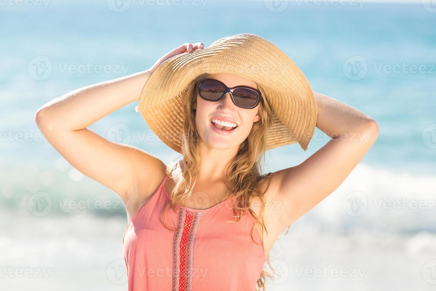 loira bonita com chapéu de palha olhando para a câmera foto