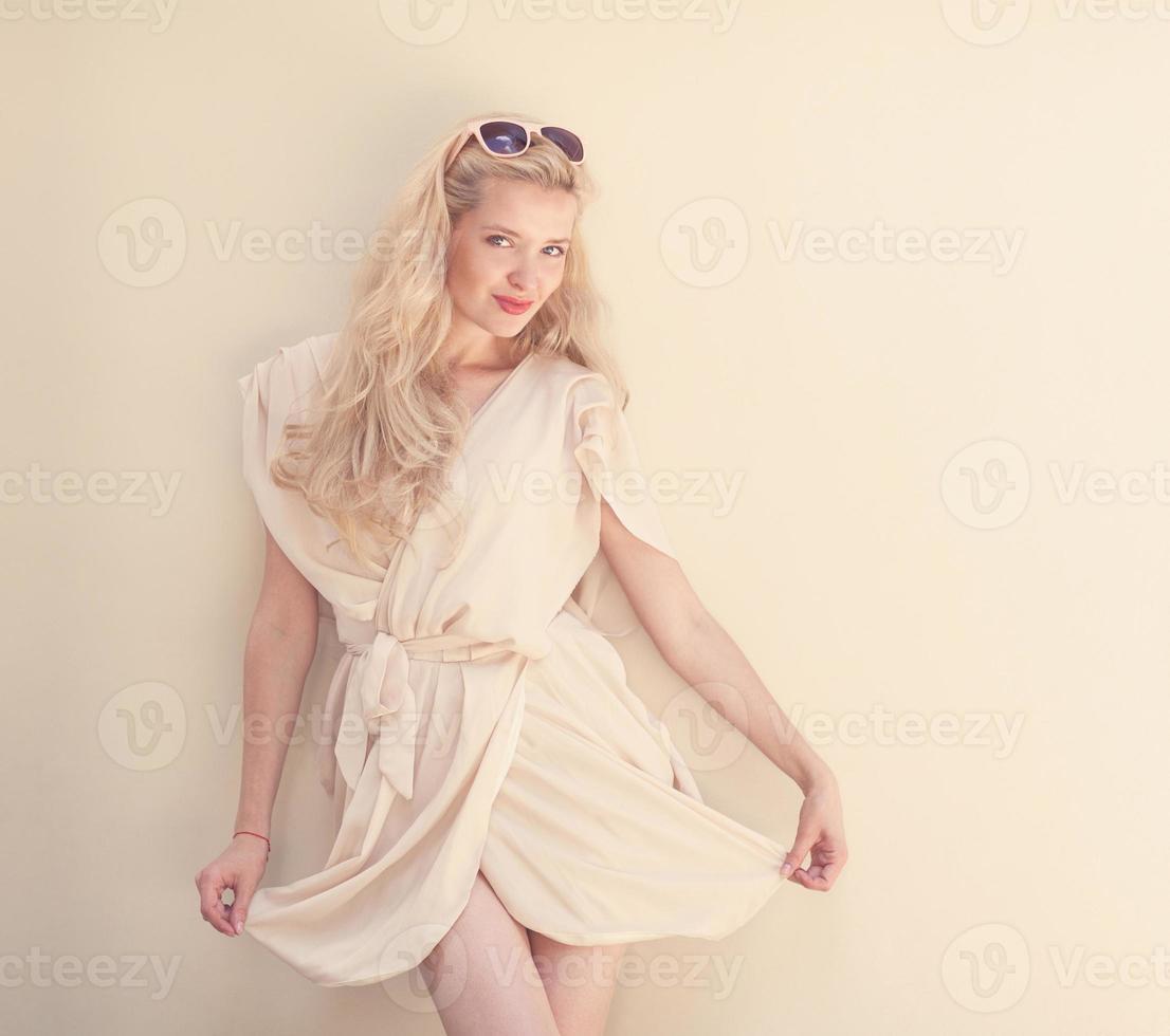 retrato de verão de uma jovem loira linda em um vestido branco foto