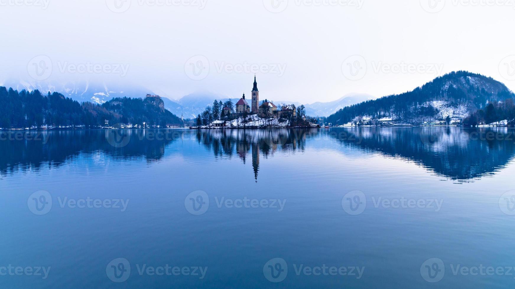 simetria perfeita de um lago e uma igreja em uma pequena ilha foto