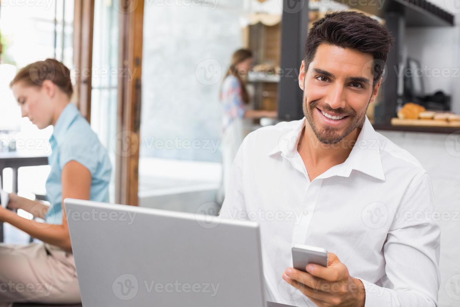 homem usando laptop e celular em uma cafeteria foto
