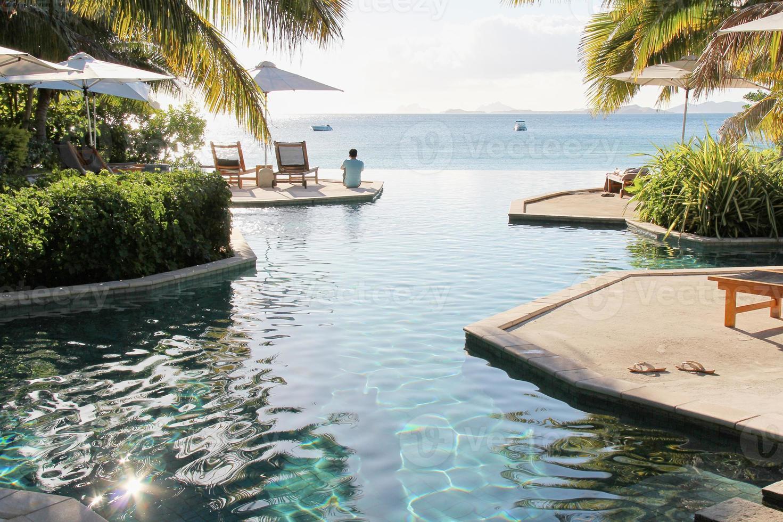 homem sentado à beira da piscina infinita em resort de praia foto