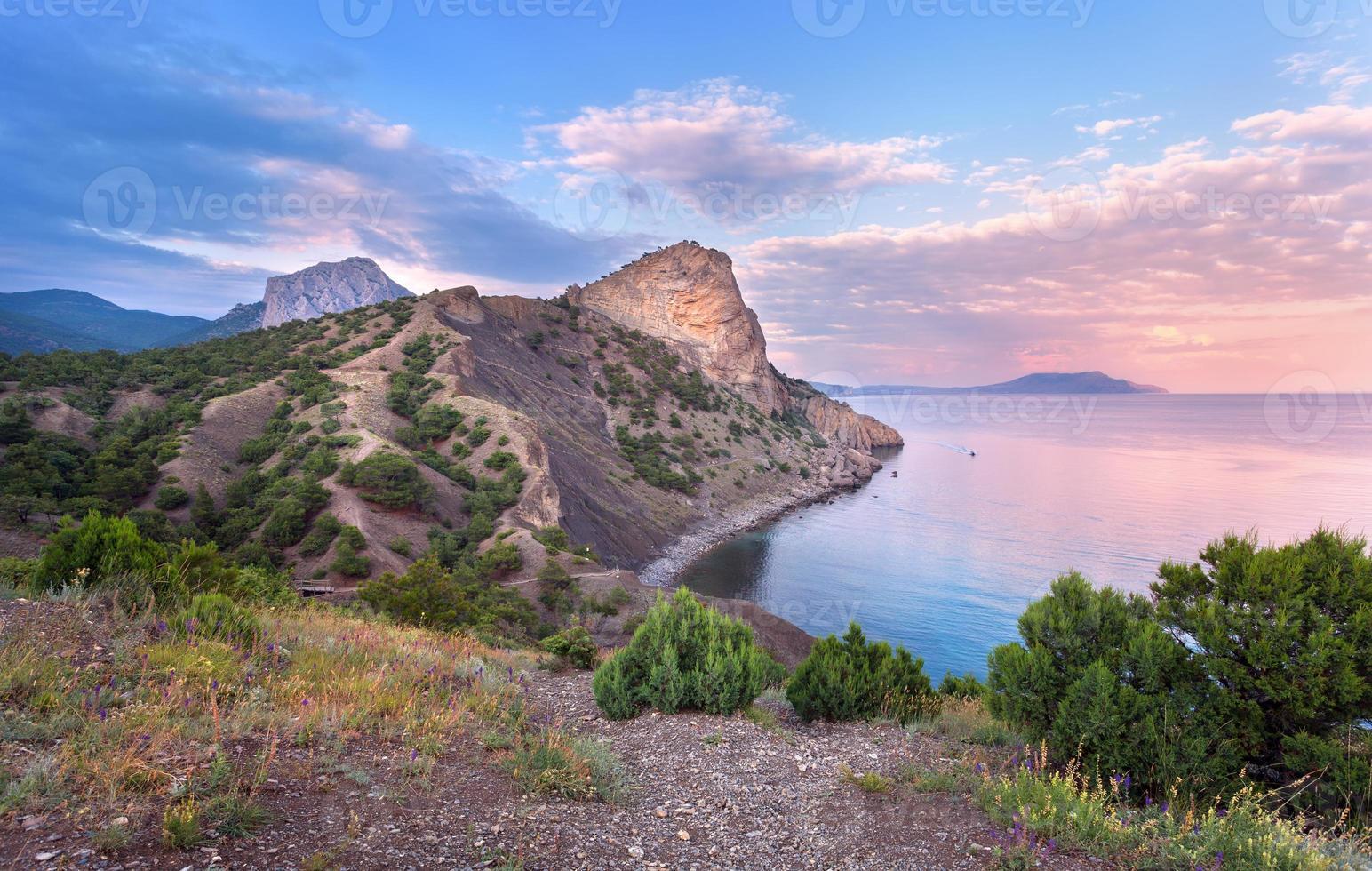 lindo pôr do sol de verão no mar com montanhas, árvores foto