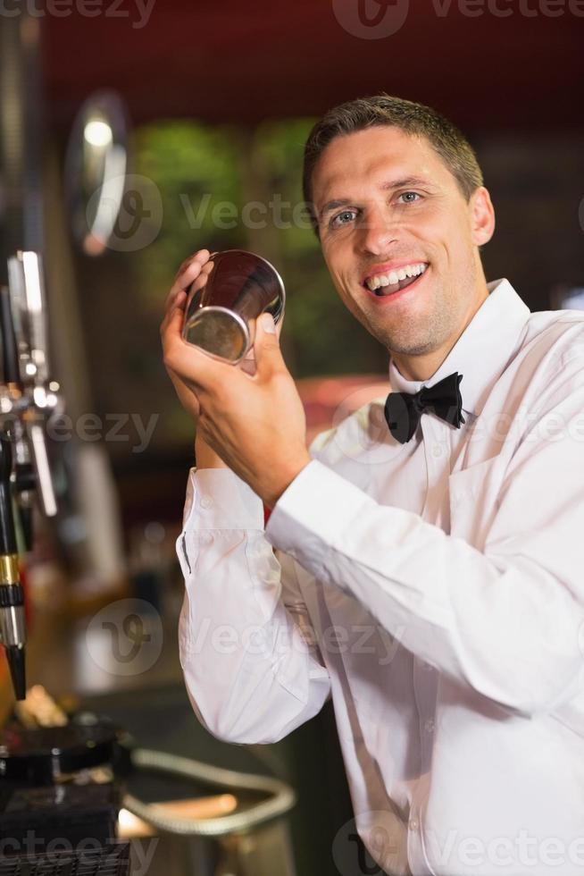 belo barman sorrindo para a câmera fazendo um coquetel foto