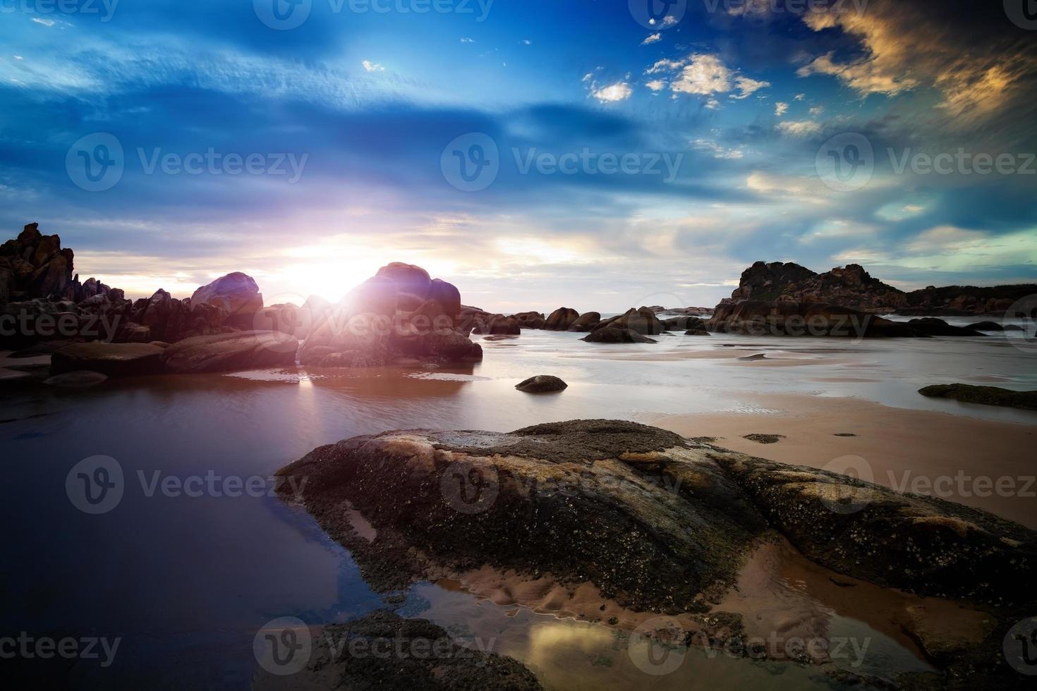 pôr do sol ao longo da costa rochosa foto