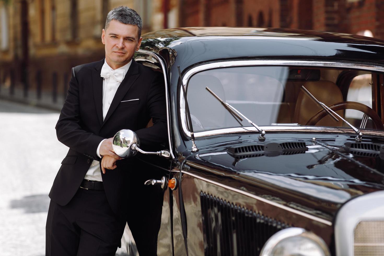 Noivo bonito em um smoking preto posando diante de um carro retrô preto foto