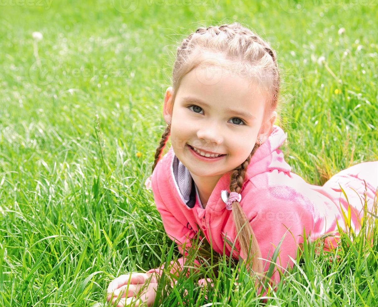 retrato de uma adorável garotinha sorridente deitada na grama foto