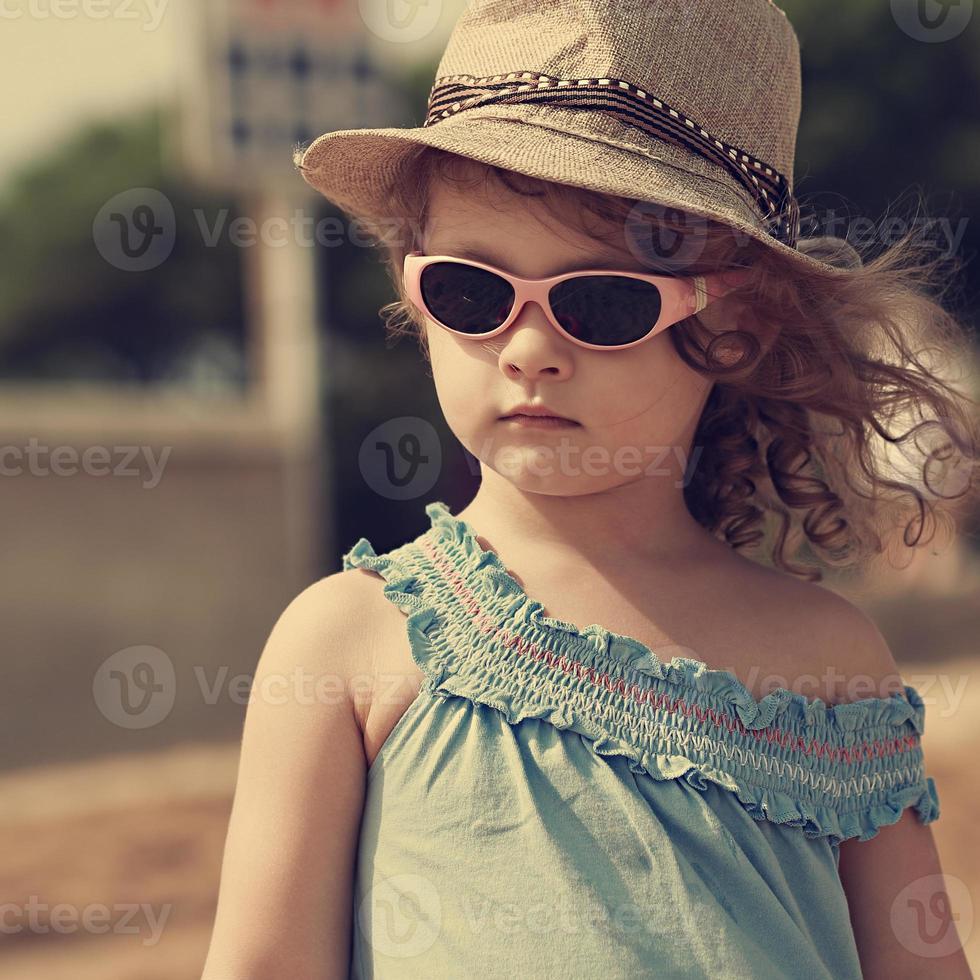 menina linda moden com chapéu e óculos de sol olhando foto