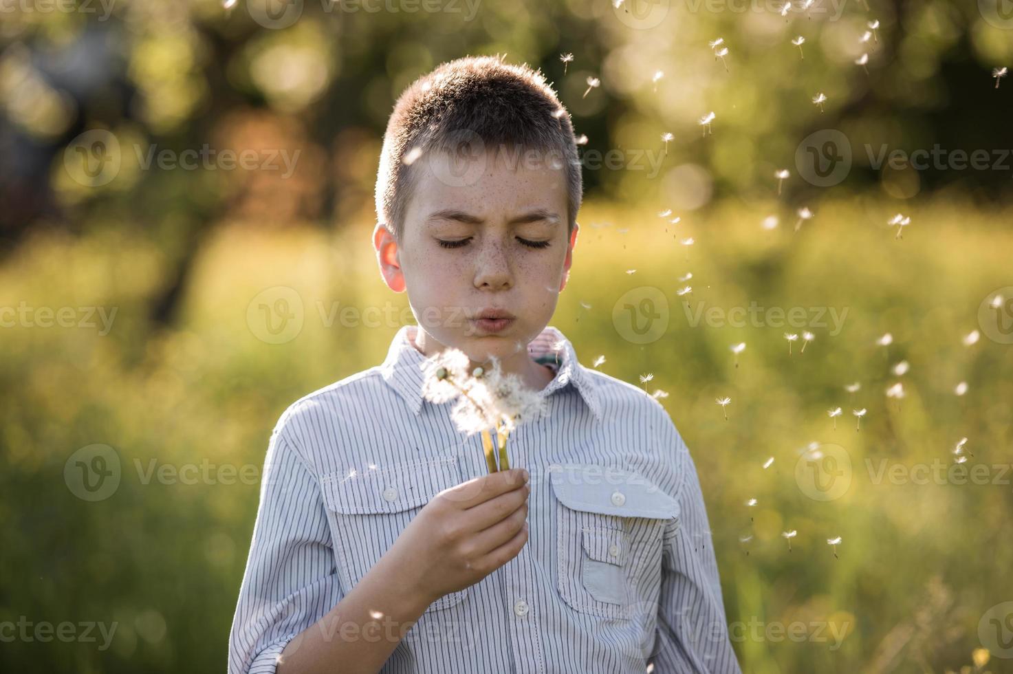 garotinho soprando dente de leão foto
