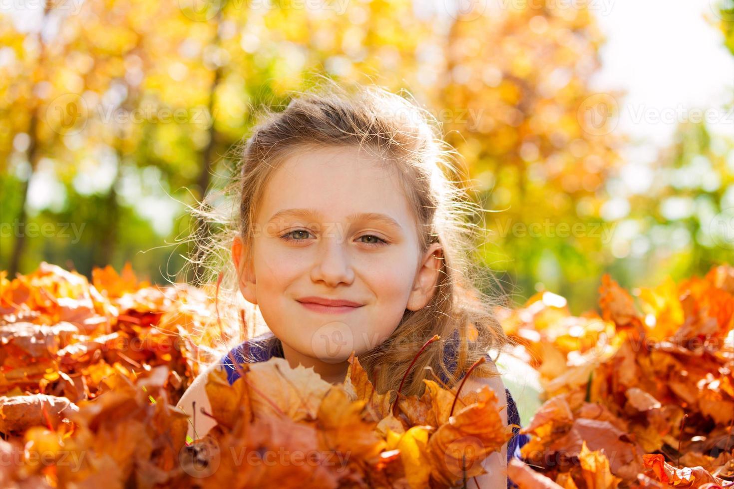 garota sorridente close-up em folhas douradas foto