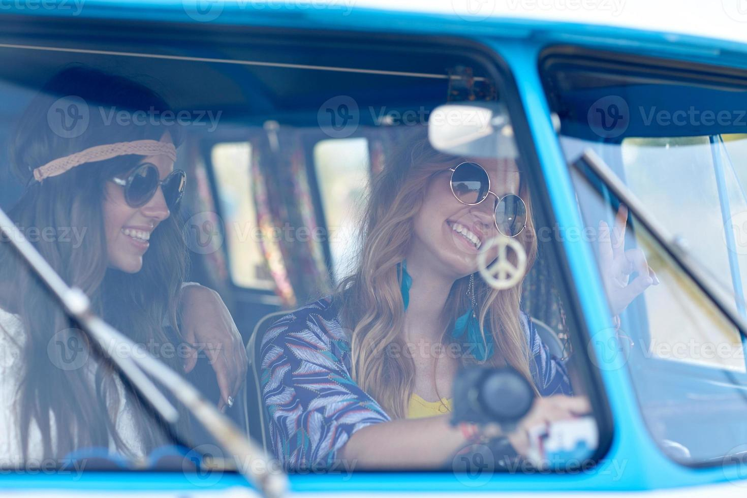 jovens hippies sorridentes dirigindo minivan foto