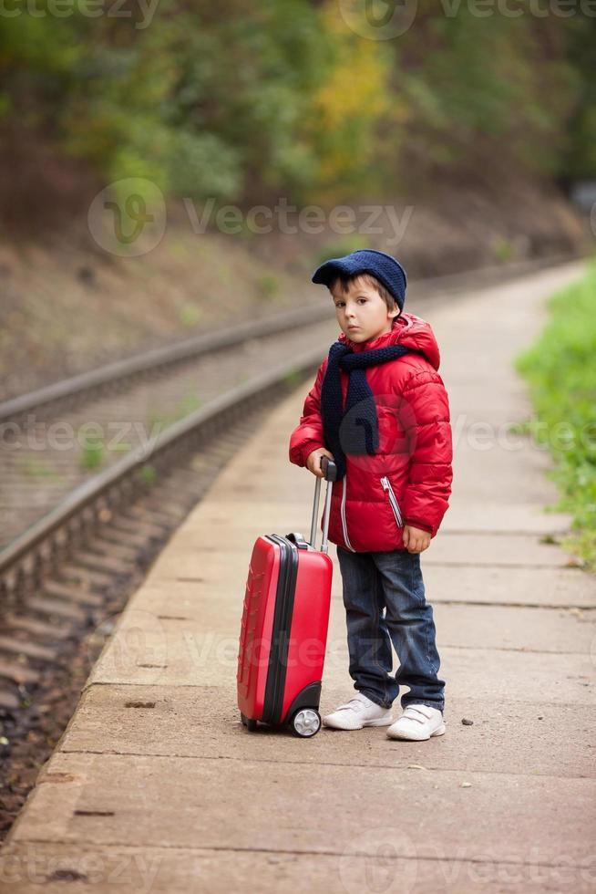 adorável criança bonitinha, garoto, esperando em uma estação de trem foto
