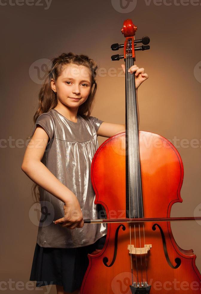 garota elegante com cabelo comprido segurando o violoncelo para tocar foto