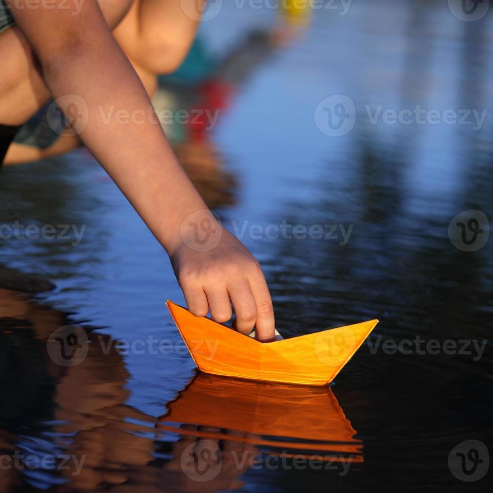 navio de papel nas mãos das crianças foto