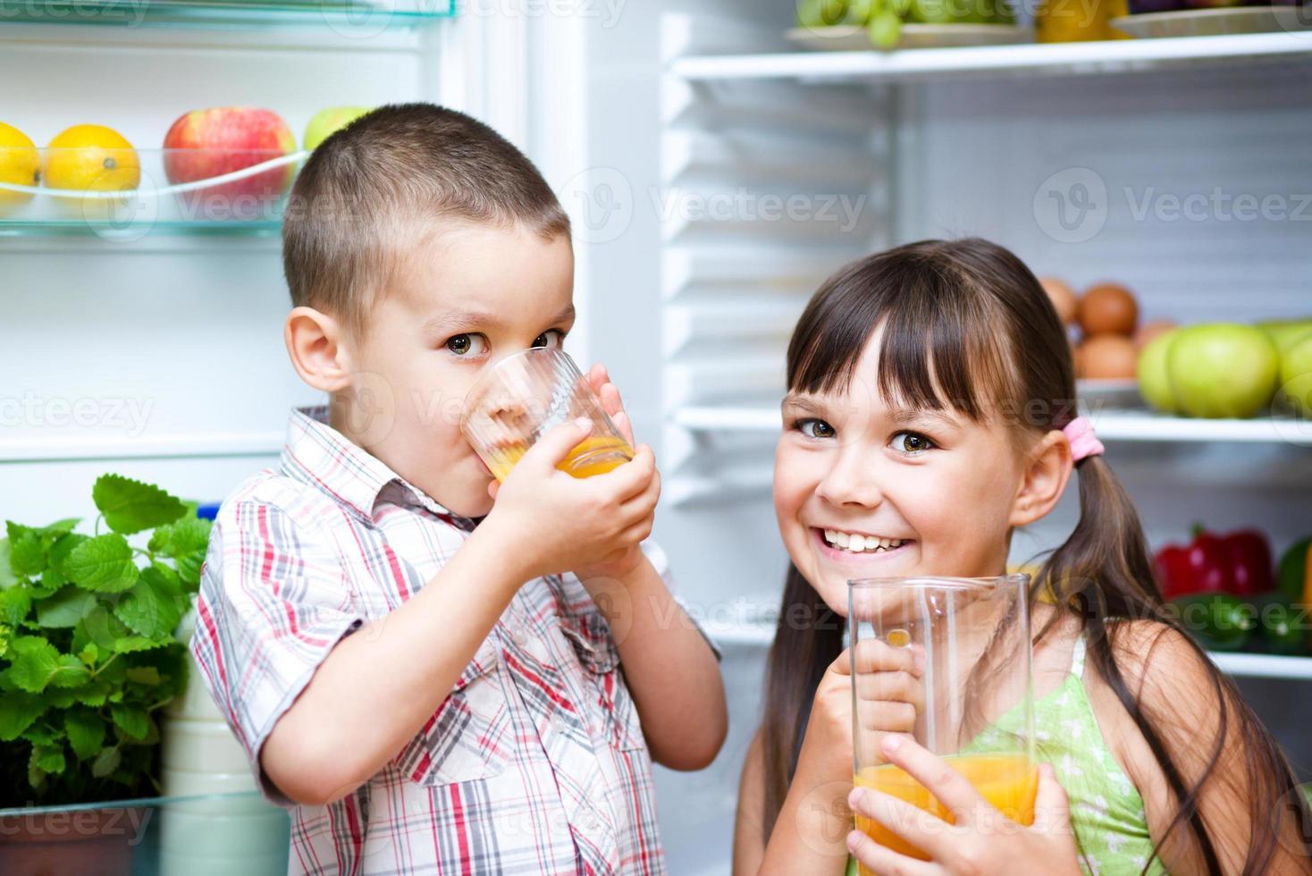 crianças bebem suco perto da geladeira foto