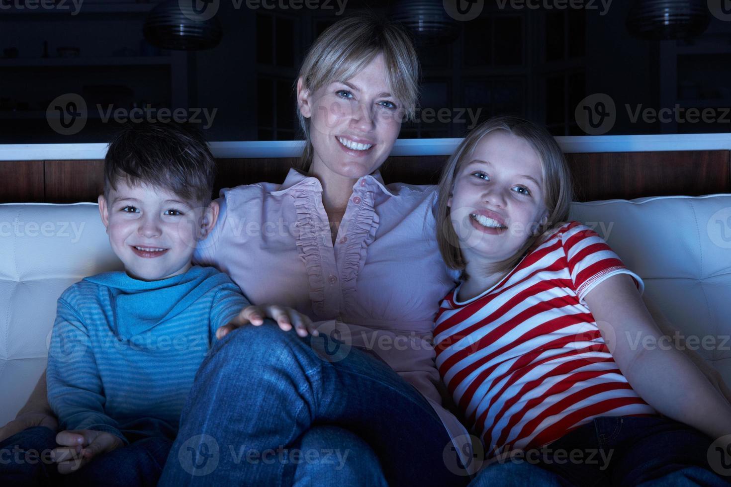mãe e filhos assistindo programa na tv sentados foto