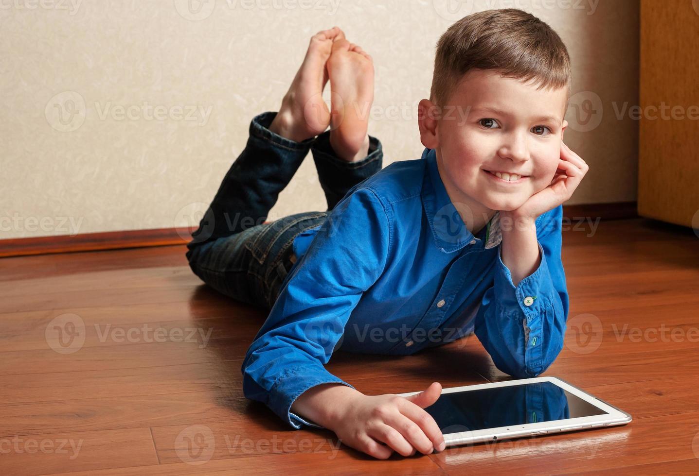 menino sorridente deitado no chão com um tablet digital foto