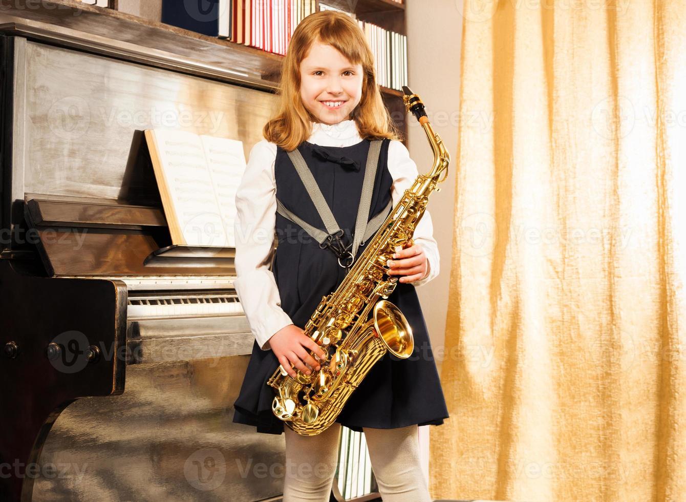 garota feliz em uniforme escolar segurando saxofone alto foto