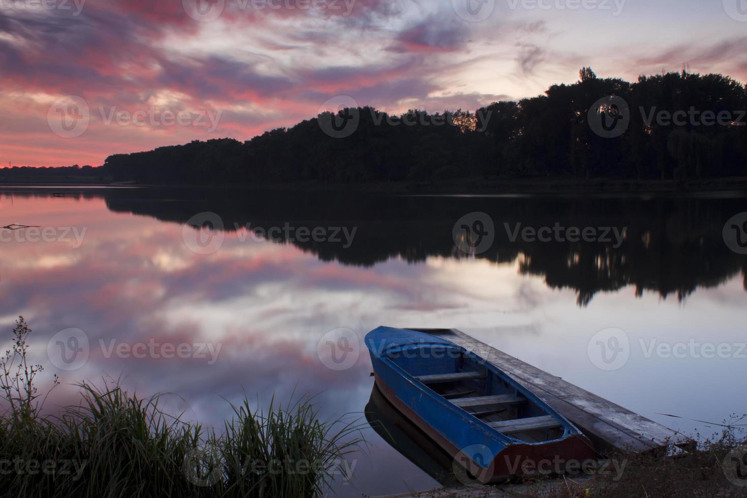 lindo amanhecer no lago com um barco foto