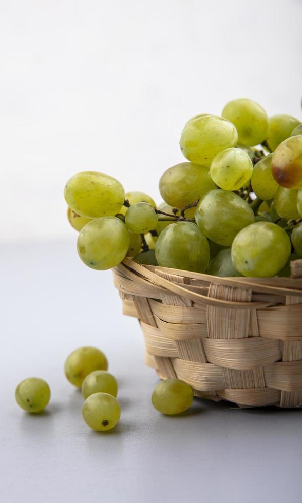 uvas brancas em uma cesta em fundo cinza foto