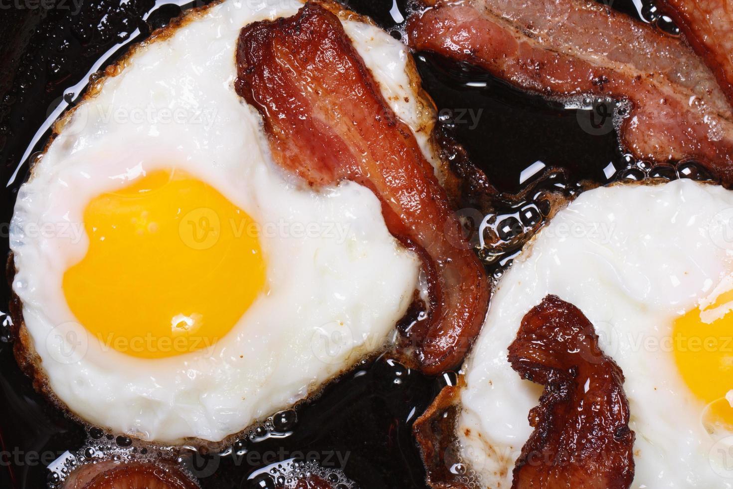 Ovos fritos com bacon em uma panela vista de cima foto