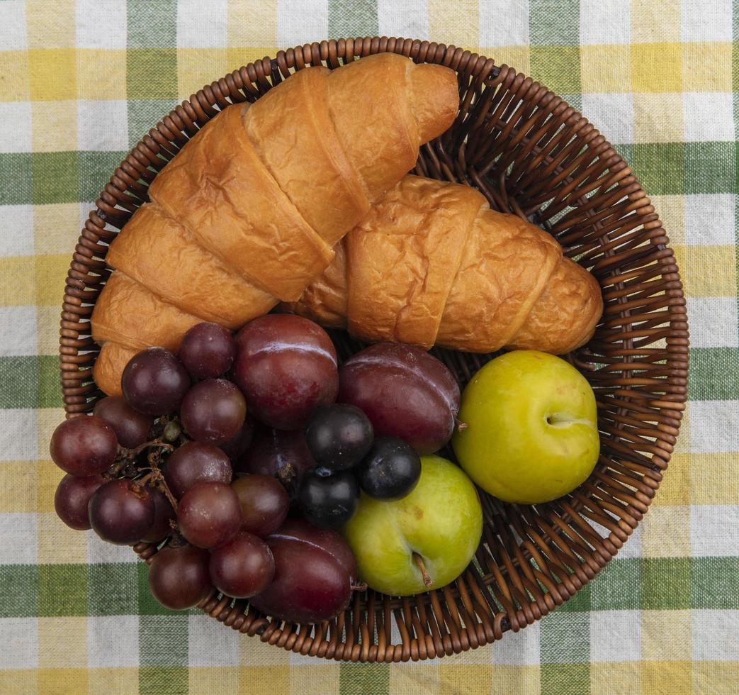 bagas com croissants em uma cesta em fundo de pano xadrez foto