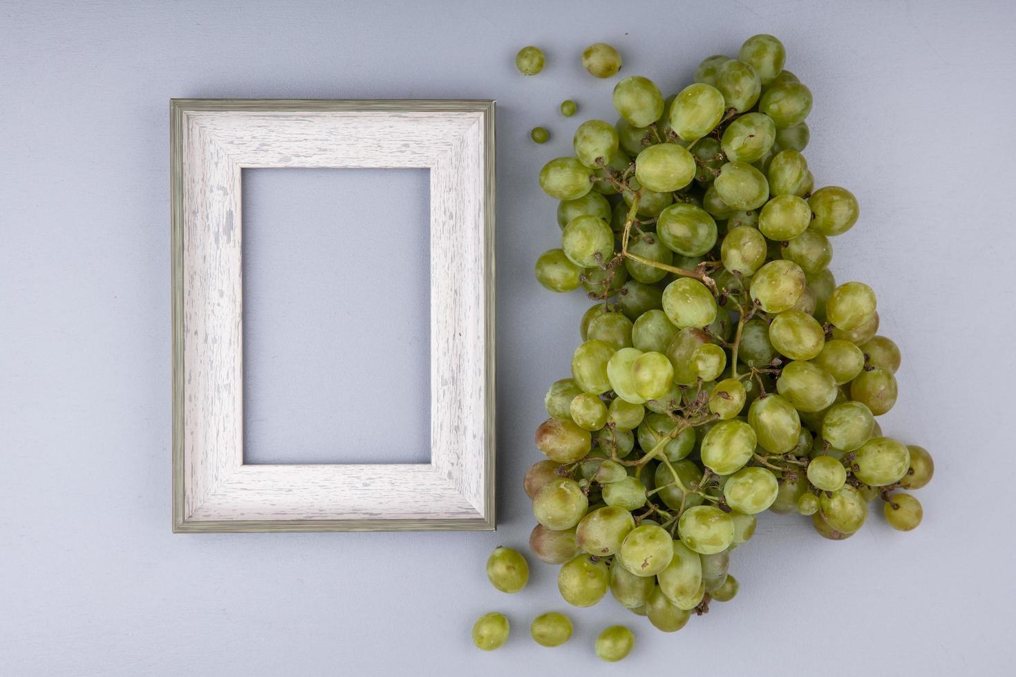 uvas brancas e moldura em fundo cinza foto