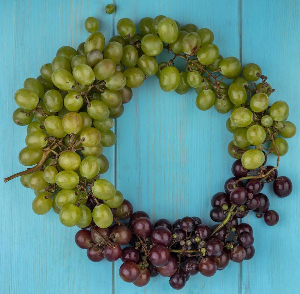 vista superior de uvas em forma redonda em fundo azul com espaço de cópia foto